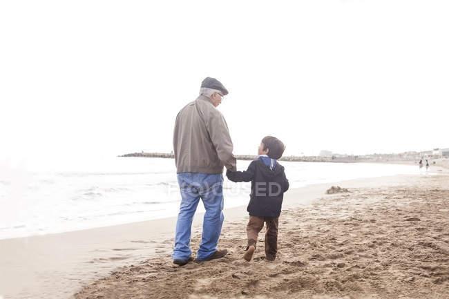 Abuelo y nieto caminando y hablando en la playa - foto de stock
