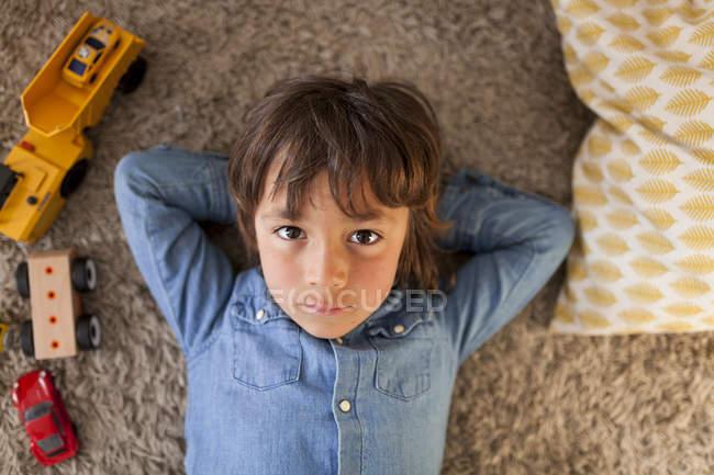 Портрет маленький хлопчик, лежачи на килимі з Іграшкові машинки Крім нього — стокове фото