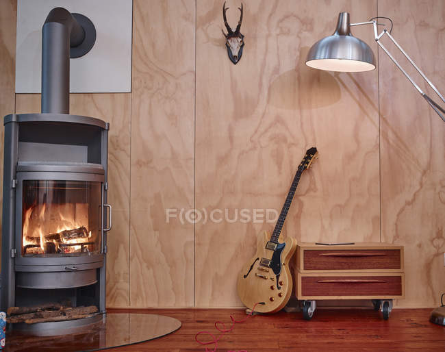Electric guitar leaning on chest of drawers near fireplace — Stock Photo