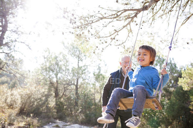 Little boy having fun on a swing while grandfather watching — Stock Photo