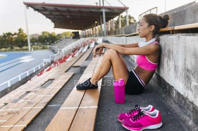 Vista lateral de esportista com fones de ouvido descansando em um estádio de atletismo — Fotografia de Stock