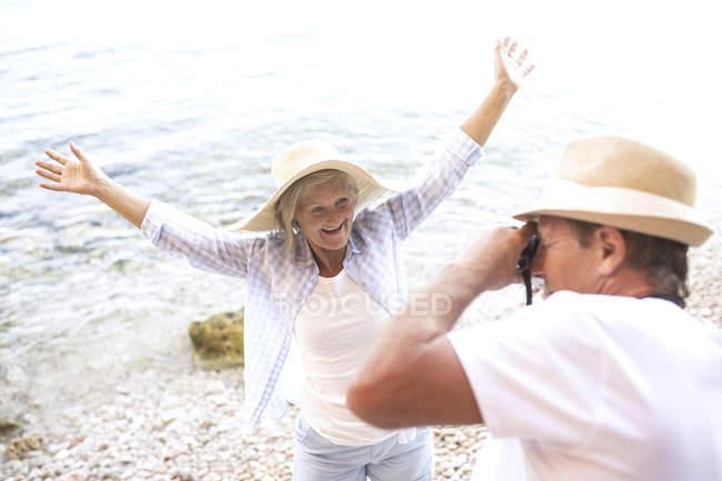 Actif mignon couple de personnes âgées prenant des photos à la caméra à la plage — Photo de stock
