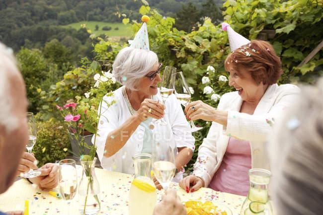 Group of seniors celebrating, drinking champagne — Stock Photo