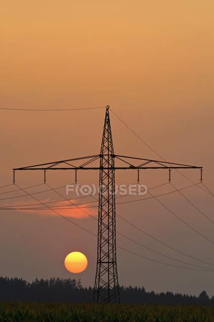 Allemagne, Bavière, pylône électrique et soleil du soir — Photo de stock