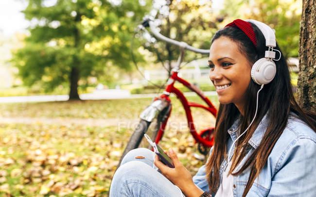 Молодая женщина слушает музыку со своим смартфоном в парке — стоковое фото