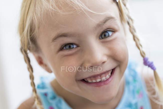 Retrato de niña sonriente con trenzas - foto de stock