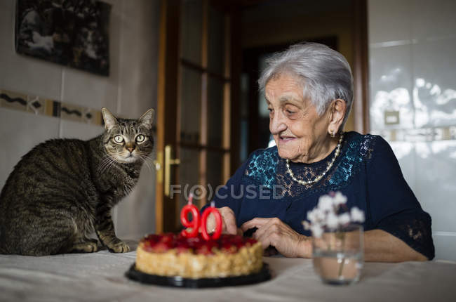 Senior woman celebrating ninetieth birthday with her cat — Stock Photo