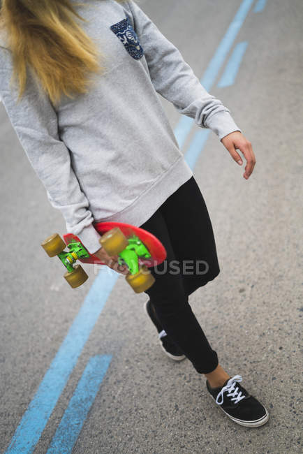 Young woman with skateboard crossing the street — Stock Photo