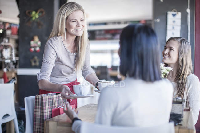 Smiling waitress serving cups of coffee in a coffee shop — Stock Photo