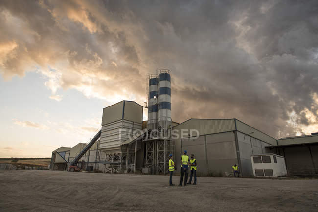 People in safety vests on industrial site — Stock Photo