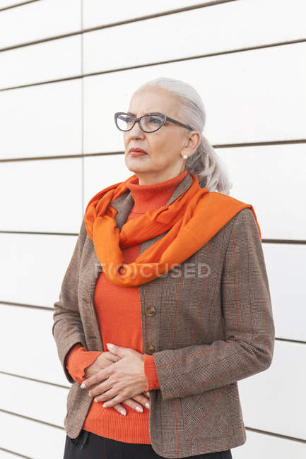 Portrait of fashionable mature woman standing in front of white wall — Stock Photo