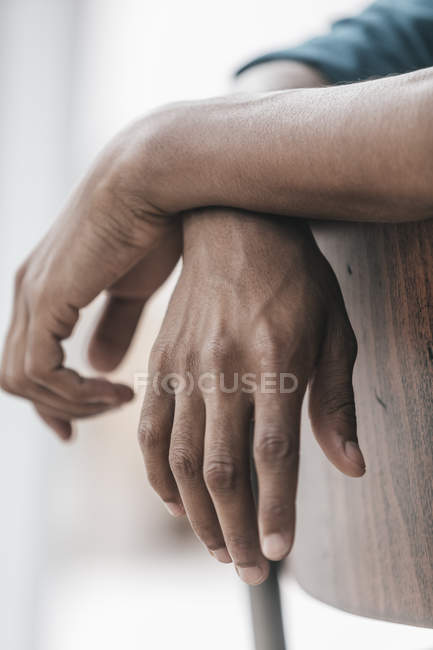 Hands of young man leaning on chair — Stock Photo