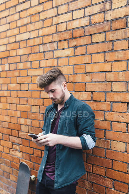 Young man with skateboard using cellphone beside break wall — Stock Photo