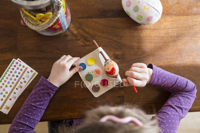 Girl painting Easter egg at wood table — Stock Photo
