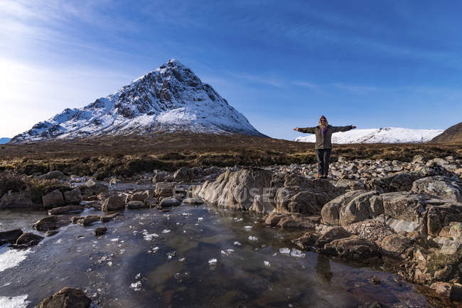 Scotland, Highlands, Glencoe, Glen Etive, woman standing in landscape with outstretched arms — Stock Photo
