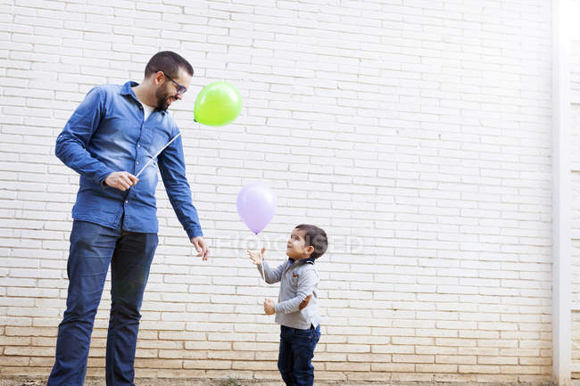 Padre y su hijito con globos delante de una pared de ladrillo blanco - foto de stock