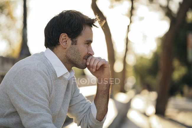 Nachdenklicher Mann sitzt mit der Hand am Kinn — Stockfoto