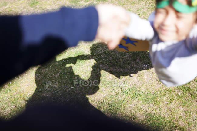 Petit garçon habillé en super héros jouant avec son père sur une prairie — Photo de stock