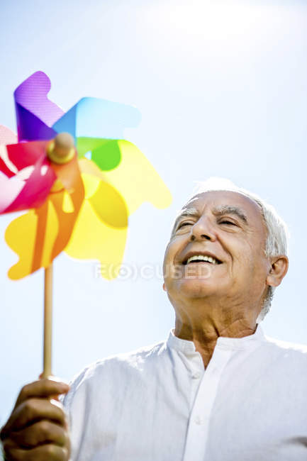 Smiling senior man holding pinwheel outdoors — Stock Photo