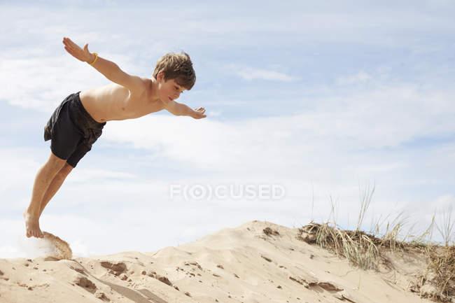 Boy am Strand Düne mit ausgestreckten Armen in die Luft springen — Stockfoto