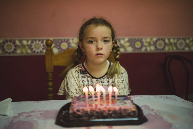 Portrait of sad little girl with birthday cake — Stock Photo