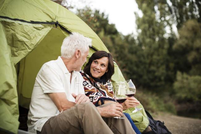 Casal sênior sentado com vinho em uma tenda — Fotografia de Stock