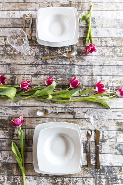 Dos lugares en la mesa decorados con tulipanes - foto de stock