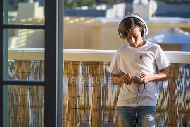 Boy listening music with headphones and smartphone on balcony — Stock Photo