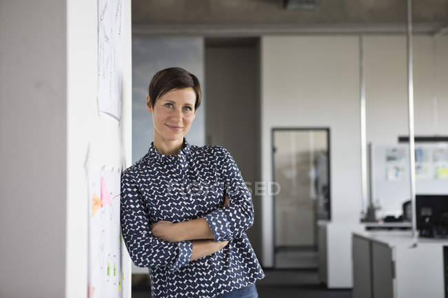 Portrait of confident businesswoman with arms crossed standing in office — Stock Photo