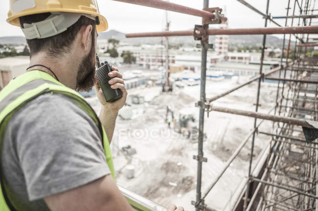 Construction worker with walkie-talkie in construction site — Stock Photo