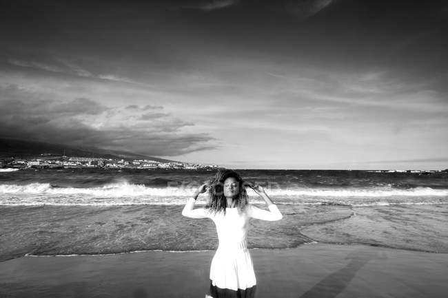 Donna con gli occhi chiusi in piedi sulla spiaggia di fronte al mare — Foto stock