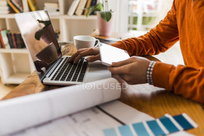 Cropped image of man using tablet and laptop at desk with color samples — Stock Photo