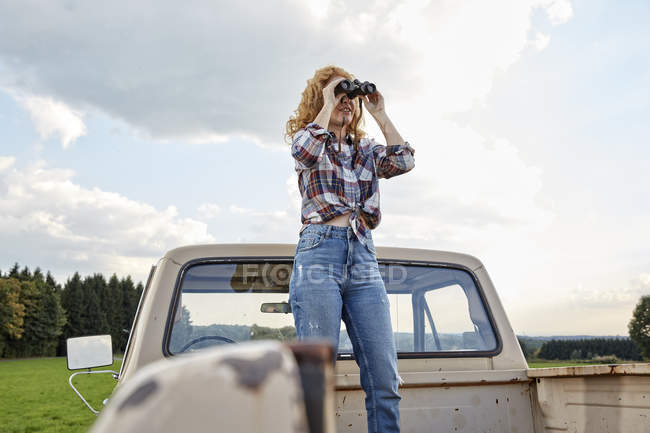 Woman standing in loading space of van and looking through binoculars — Stock Photo