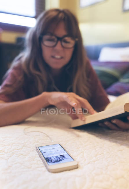 Woman in spectacles with cell phone reading a book at home — Stock Photo