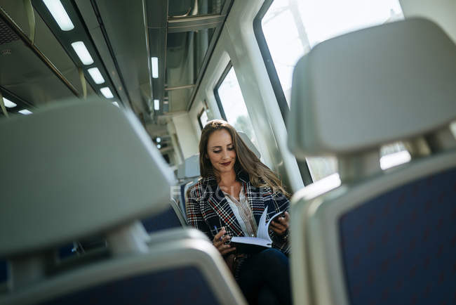 Attractive caucasian businesswoman on a train with notebook — Stock Photo