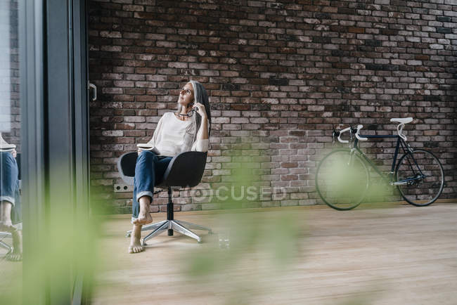 Woman with long grey hair sitting on chair at window — Stock Photo