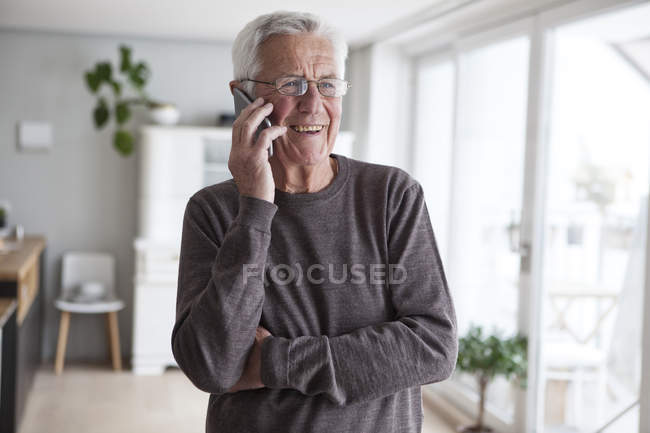 Portrait of smiling senior man telephoning with smartphone at home — Stock Photo