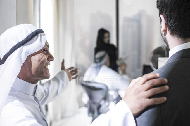 Middle Eastern businessman inviting Western partner into office — Stock Photo