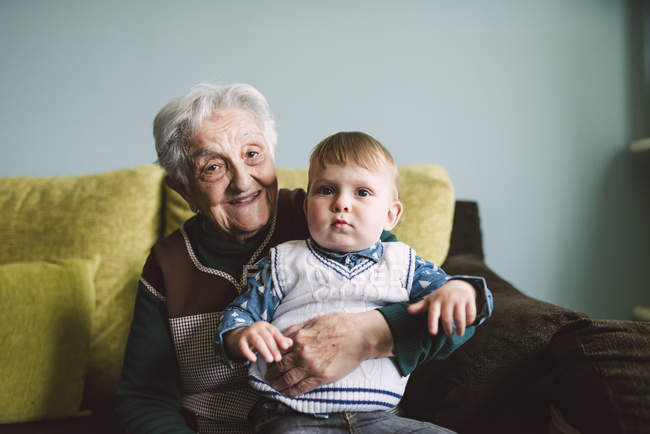 Old woman and her great-grandson sitting on the couch — Stock Photo