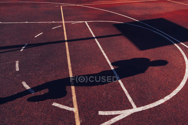 Shadow of basketball player on sport field — Stock Photo