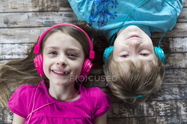 Portrait of boy and girl listening music with headphones — Stock Photo