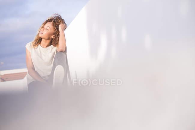 Жінка з закритими очима її до стіни, насолоджуючись сонячними променями — стокове фото