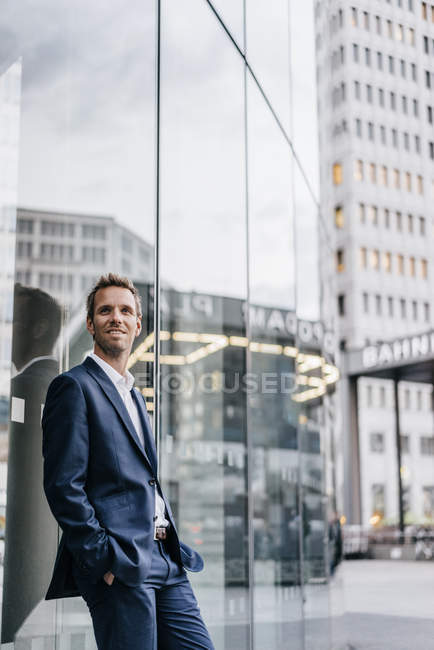 Portrait of confident businessman leaning against glass facade — Stock Photo
