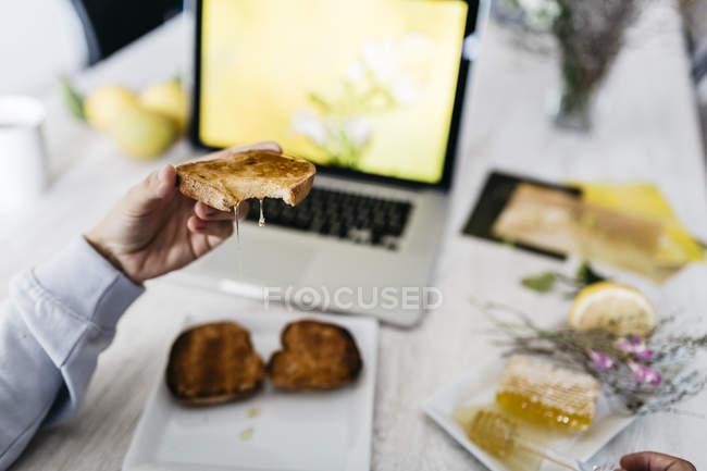 Рука людини проведення покусав тост з медом капала на своєму робочому місці, Закри — стокове фото