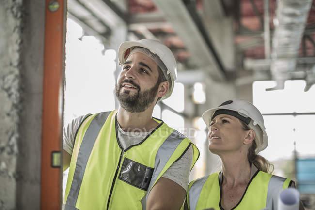 Женщина с строителем, используя уровень воды в строительной площадки — стоковое фото