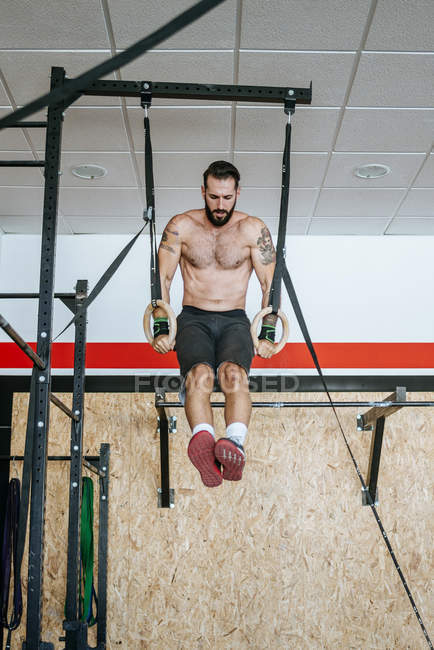 Man doing exercises on rings in gym — Stock Photo