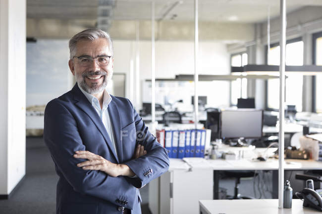 Portrait of confident businessman standing in office with arms crossed — Stock Photo