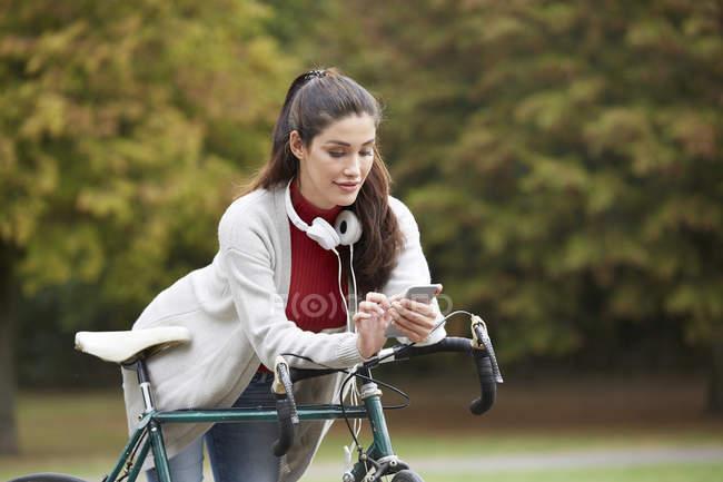 Mujer con bicicleta en el parque otoñal mensajería de texto con smartphone - foto de stock