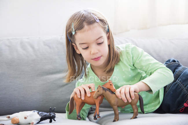 Little girl lying on couch and playing with animal figurines — Stock Photo