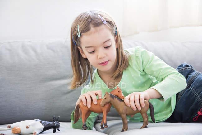 Маленькая девочка лежит на диване и играет с фигурками животных — стоковое фото